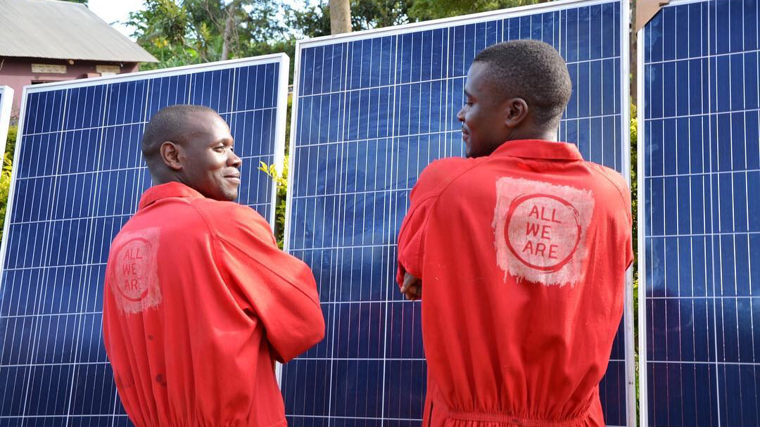 Two All We Are employees install a solar panel