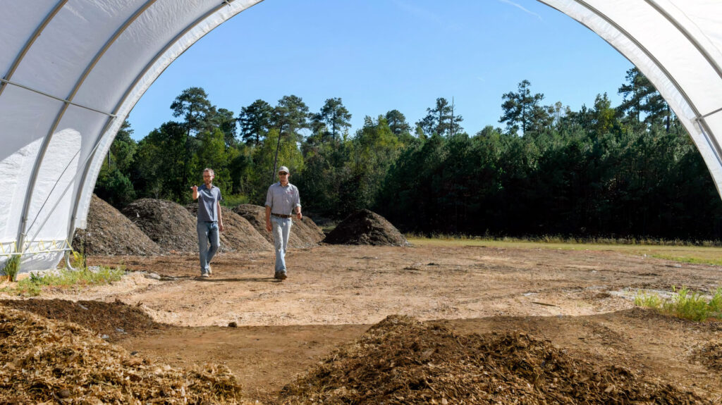 Two men look at compost at NCState