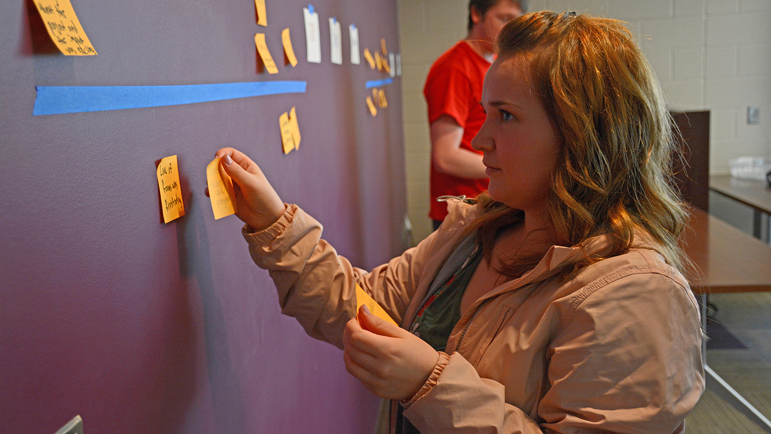 A Fellow puts a sticky note on the wall during a team-building activity.