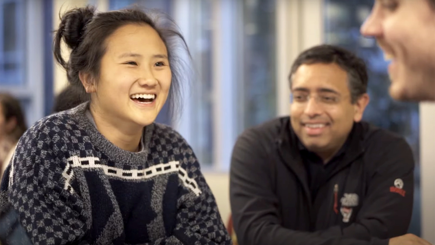 A still image to a video shows a Social Innovation Fellow talking with fellow students.