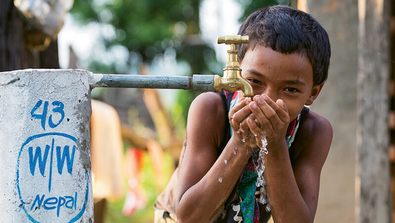 Boy drinks from water tap