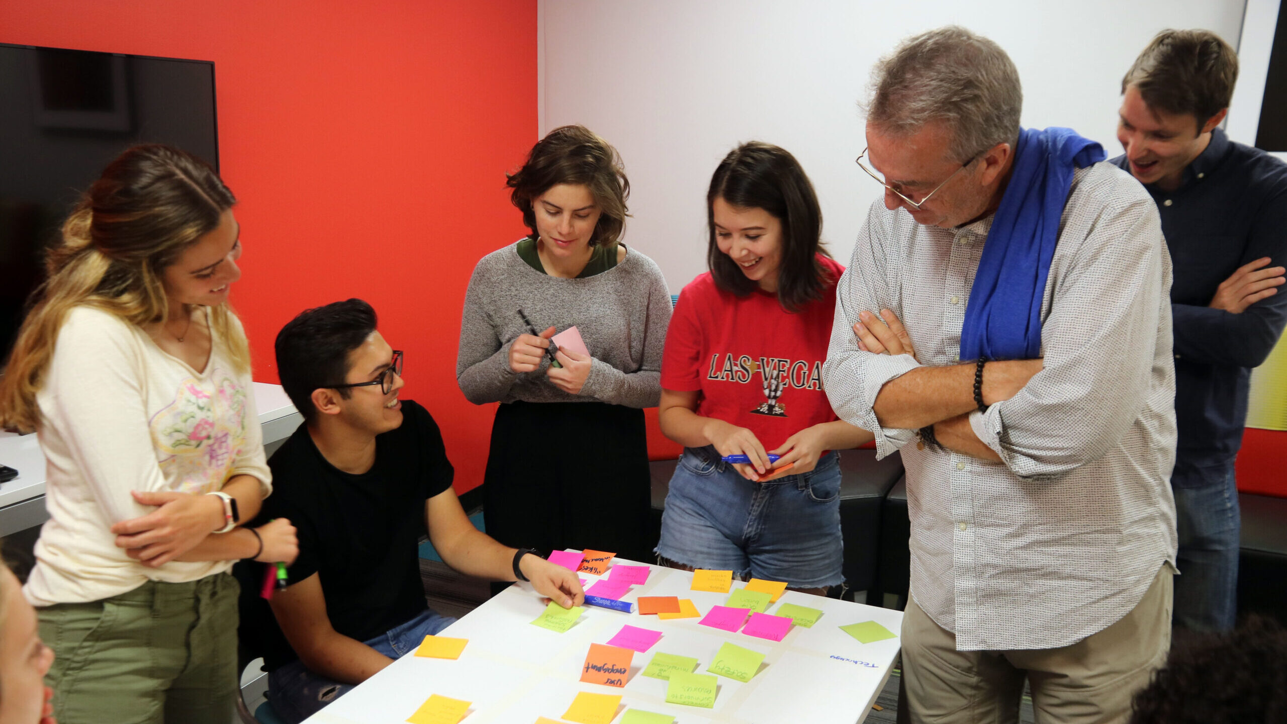 A group of Fellows work with Post-it notes and laugh
