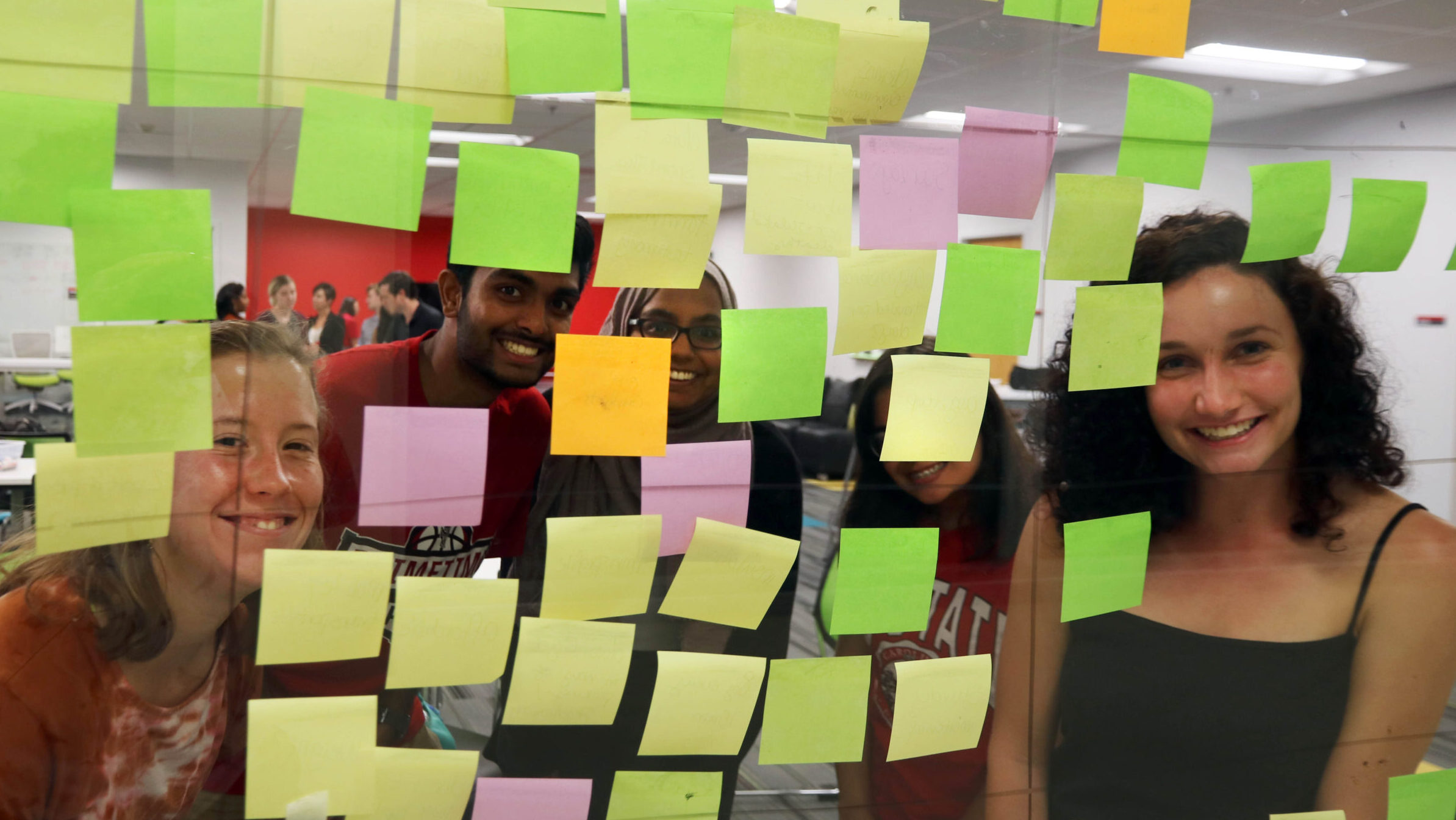 Social Innovation Fellows smile while placing post-it notes